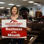 Owner Lynette Burns stands in her store with sign that says business of the month.