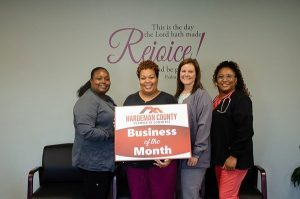 Staff of Miracle Healthcare in their office holding Business of the Month sign.