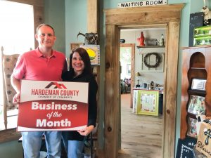 Image of business owners holding business of the month sign.